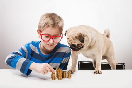 Funny boy and his dog looking at piles of coins photo