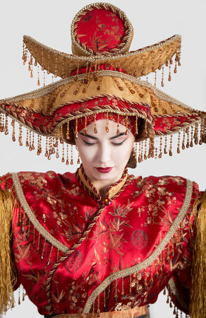 historical periods: Portrait of a woman with closed eyes in Chinese princess costume, gray background Stock Photo