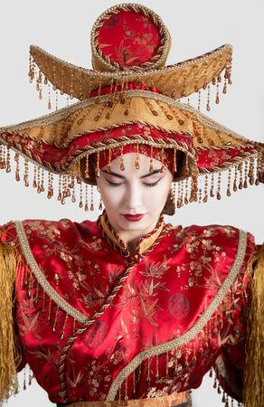 vestidos de epoca: Retrato de una mujer con los ojos cerrados en traje de princesa china, fondo gris Foto de archivo