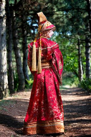 vestidos de epoca: Mujer en traje de la princesa china caminando en el bosque de pinos, vista desde la parte trasera