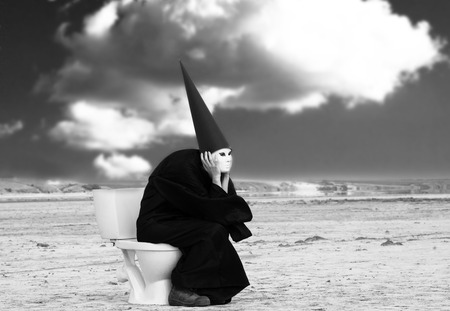 Strange person in black cloak sitting on the toilet and thinking in the middle of the desert