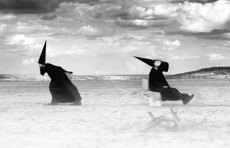 grotesque: Two strange persons in black cloaks traveling in the desert