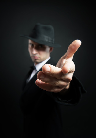 Man in the black trench coat and hat stretching his hand toward the camera Stock Photo