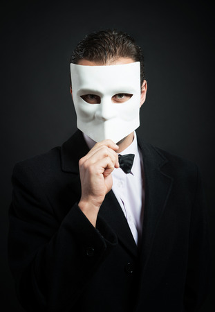 Man holding a mask in front of his face photo