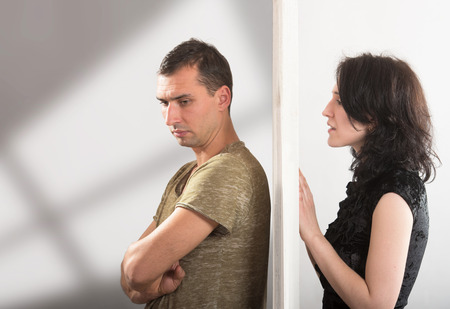 relationship problem: Conflict between man and woman standing on either side of a door Stock Photo