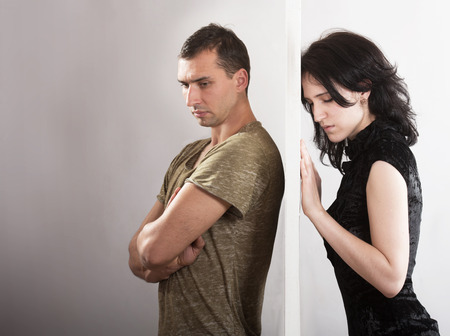 Conflict between man and woman standing on either side of a door Stock Photo