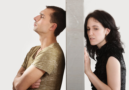 severance: Conflict between man and woman standing on either side of a wall Stock Photo