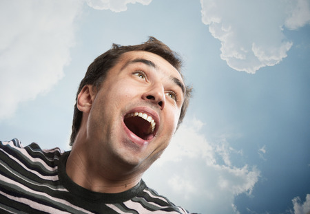exultation: Portrait of a joyful man looking up against a sky background