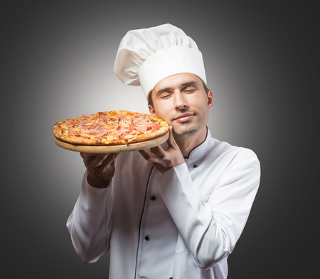 Studio portrait of a chef with closed eyes smelling pizza