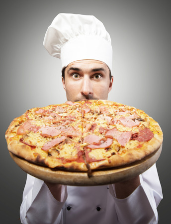 Humorous portrait of a man in chef s hat smelling pizza photo