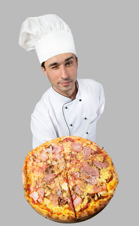 Humorous portrait of a winking man in chef s hat showing pizza, view from above