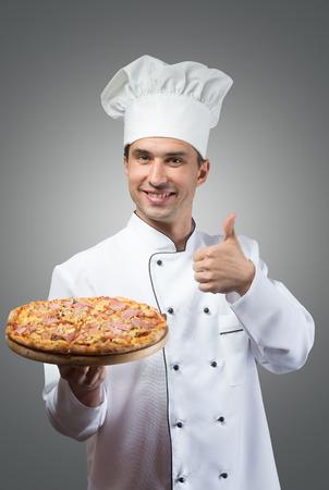 Portrait d'un chef souriant avec la pizza fraîche montrant thumbs up