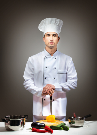 culinary skills: Portrait of a man in chefwear in a kitchen looking at camera