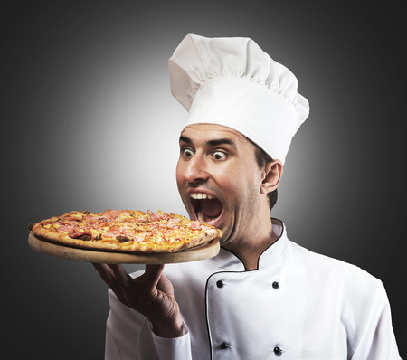 Humorous portrait of a male chef with opened mouth looking at pizza, gray background photo