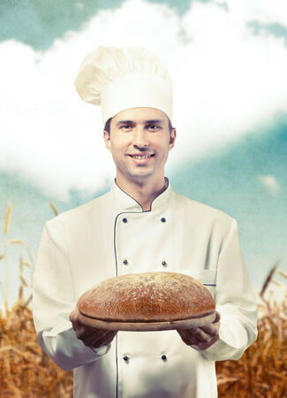 culinary skills: Portrait of a baker holding a loaf of bread against a wheat field background
