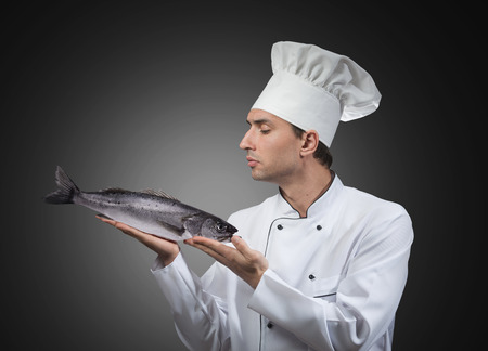 Portrait of a chef looking at the fish in his hands photo