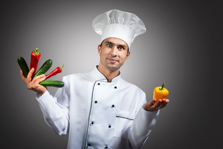 culinary skills: Humorous portrait of a chef with vegetables in his hands looking at camera