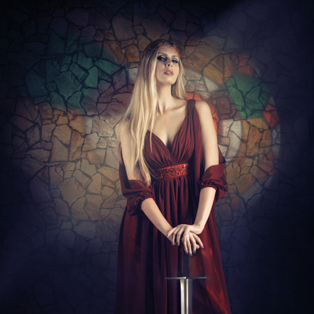 warrior woman: Fantasy style portrait of a woman in medieval dress with the sword looking at camera Stock Photo