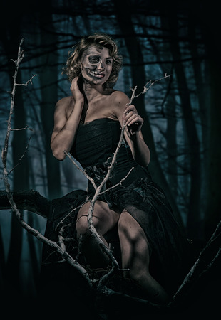 Portrait of a retro woman with skull make-up in the night forest photo