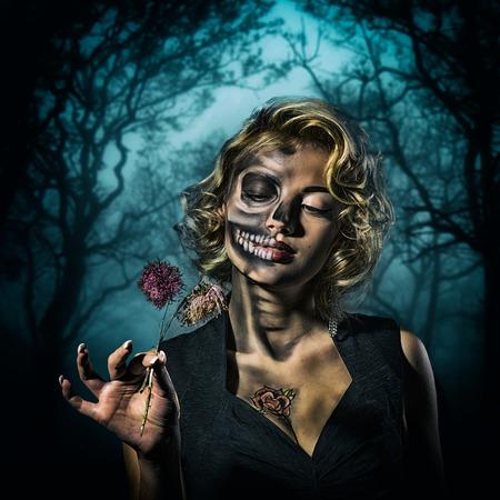 maquillaje fantasia: Retrato de una mujer retro con el cráneo de maquillaje y flores secas en la mano en el bosque de la noche