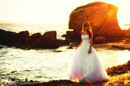 puffy: Beautiful bride walking along the seaside at sunset