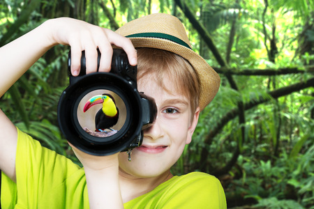 Young photographer with a camera pointing the lens directly at the viewer photo