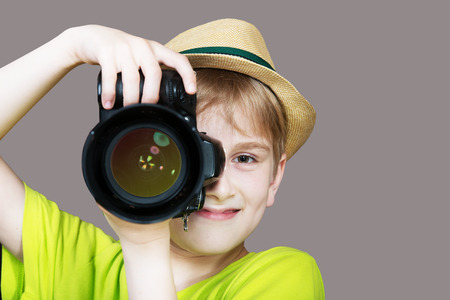capture: Young photographer with a camera pointing the lens directly at the viewer, gray background Stock Photo