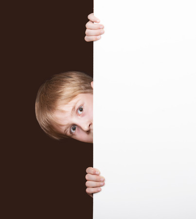 'hide out': Surprised boy looking around the corner