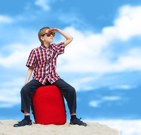 lost child: Portrait of a lost boy with his luggage, tropical beach background Stock Photo