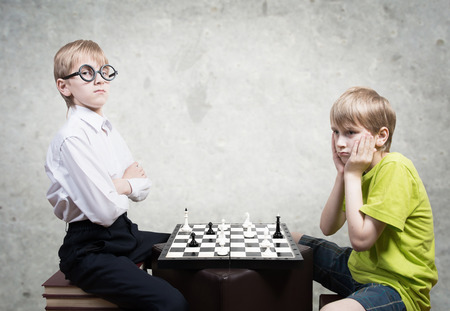 Boy and nerd playing chess photo