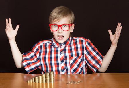 bolsa dinero: Muchacho expresivo con los montones de monedas delante de él mirando a la cámara