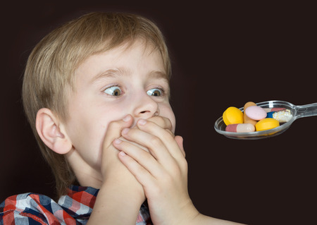 Boy refusing to take medicine on a spoon Foto de archivo