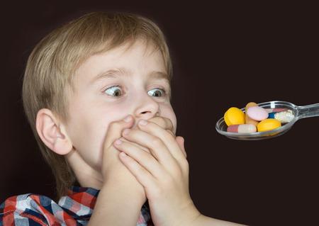 Boy refusing to take medicine on a spoon Standard-Bild