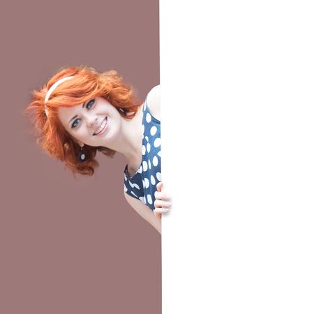 Smiling redheaded girl looking around the corner photo