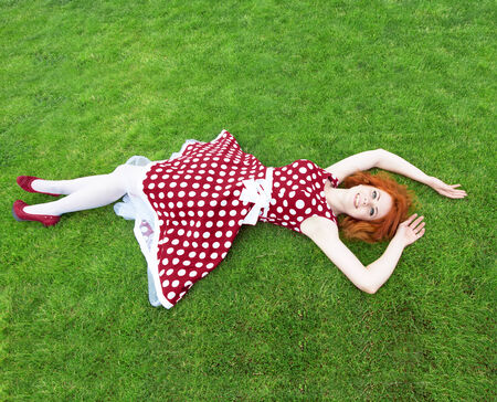 lying on back: Smiling redheaded girl lying on the grass, view from above