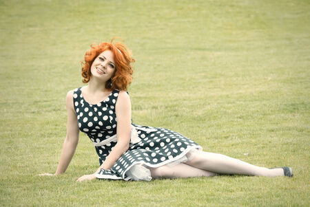 grass plot: Smiling redheaded girl sitting on the grass and smiling