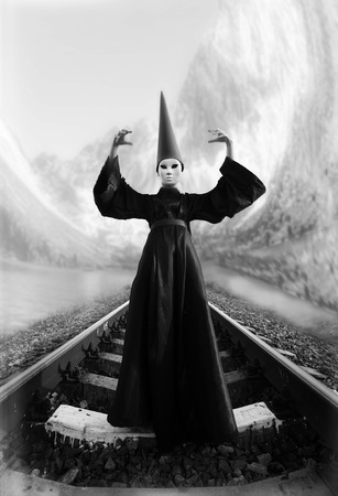 dunce cap: Wizard in black cloak and dunce hat standing on rails. Black and white image