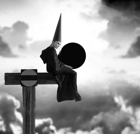 Eclipse. Strange person in black cloak and dunce hat with dark moon in her hands. Black and white image photo