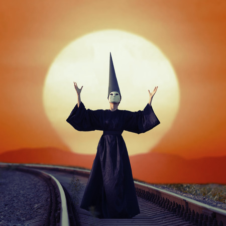 Wizard in black cloak and dunce hat standing on rails at sunset photo