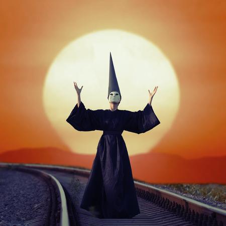 unreal unknown: Wizard in nero mantello e cappello asino in piedi su rotaie al tramonto