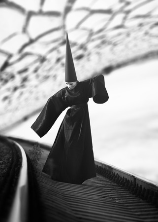Strange person in black cloak and dunce hat standing on rails and looking at a plant. Black and white image photo