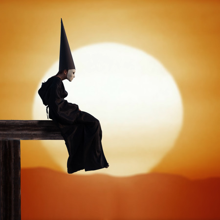 stranger: Portrait of a strange person in black cloak and dunce hat at sunset