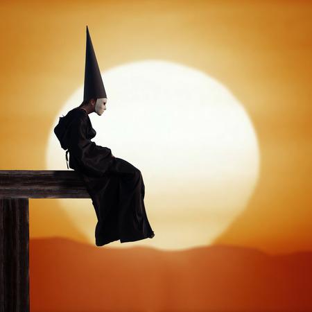unreal unknown: Ritratto di una persona strana in mantello nero e cappello asino al tramonto