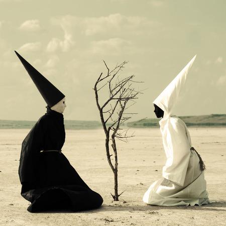ser humano: Dos personas misteriosas que se sientan a cada lado de un árbol seco en el desierto