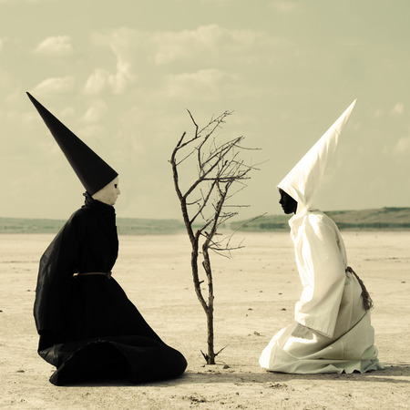 dunce cap: Two mysterious persons sitting on either side of a dry tree in the desert