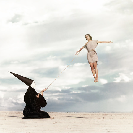 Woman flying like a kite driven by mysterious person dressed in the black cloak photo