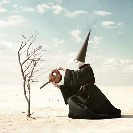unreal unknown: Misterioso personaggio con la maschera e il cappello somaro che innaffia una pianta secca con serbatoio vuoto Archivio Fotografico