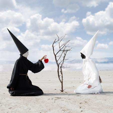 unreal unknown: Mysterious person dressed in black giving an apple from the dry tree to another person dressed in white