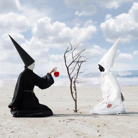 unreal unknown: Persona misterioso vestito di nero che d� una mela dall'albero secco ad un'altra persona vestita di bianco Archivio Fotografico