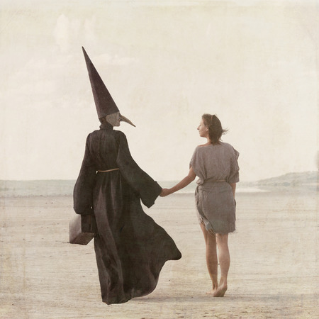 dunce cap: Woman walking away through the desert accompanied by the mysterious person in the plague mask, view from back